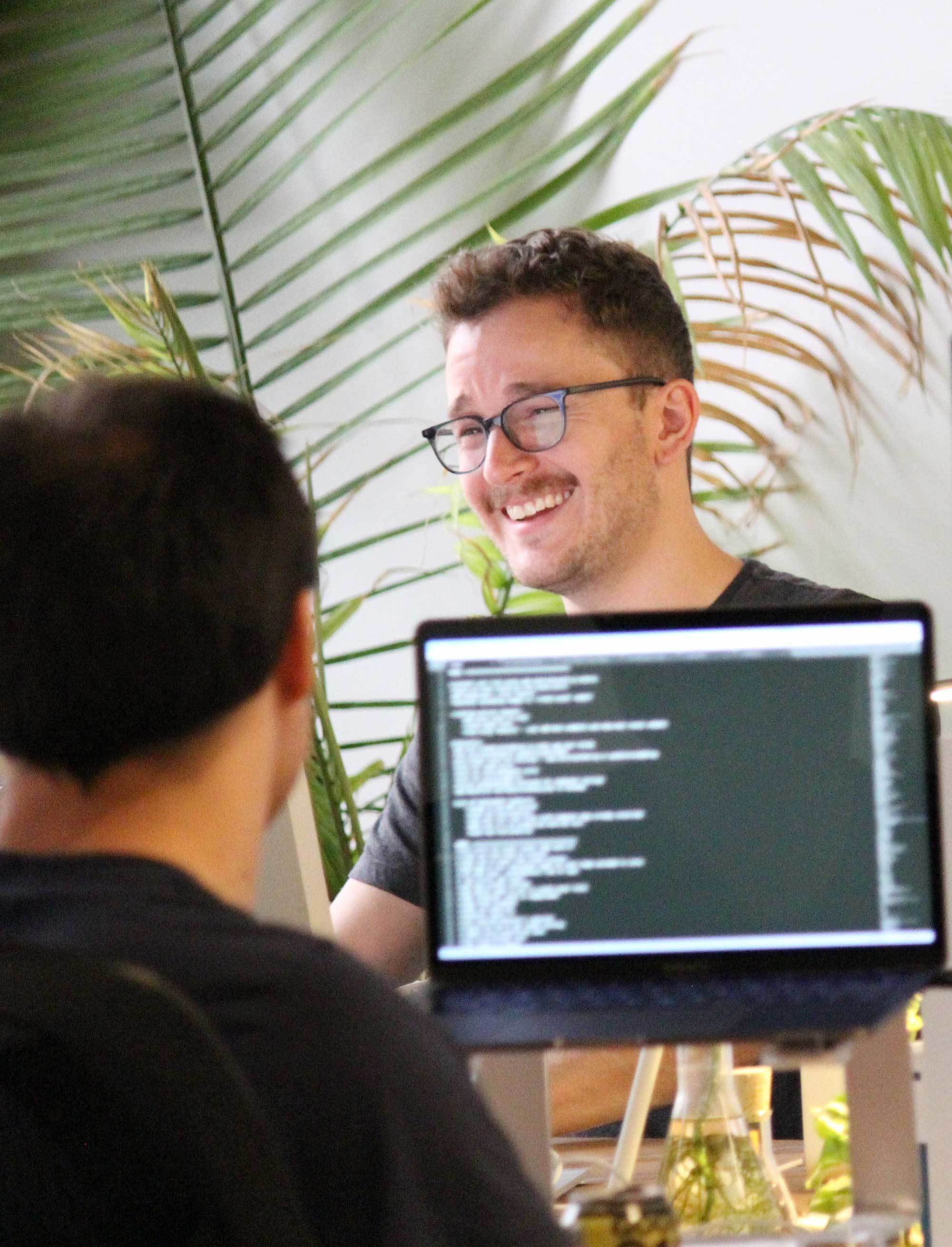 Photo of a Crema employee coding and another behind him smiling